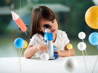 dziewczynka patrzy przez mikroskop