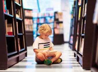 chłopiec czyta książki w bibliotece
