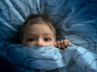 mały chłopiec w łóżku nie śpi