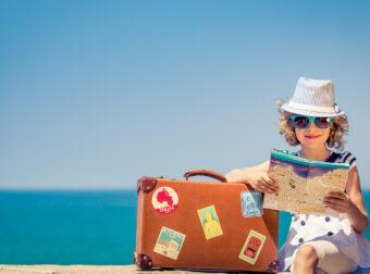 Dziecko z walizką nad morzem